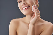 Close up cropped photo of adorable, smiling lady with naked shoulders standing isolated on gray background. She removing make-up using soft cotton pad