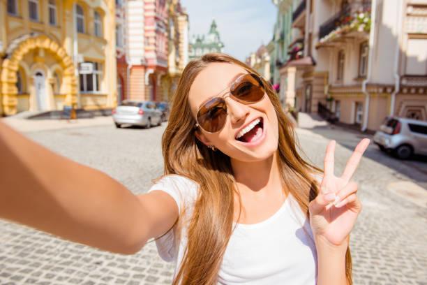 hübsche junge frau in gläsern machen selfie und shwing zwei finger - happy weekend bilder stock-fotos und bilder