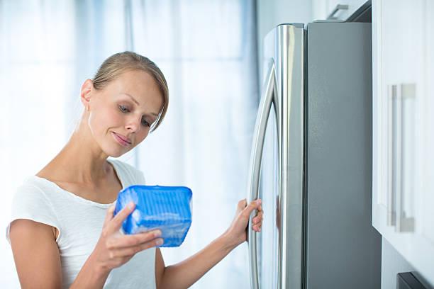 hübsche, junge frau in ihrer küche von kühlschrank - zum totlachen stock-fotos und bilder