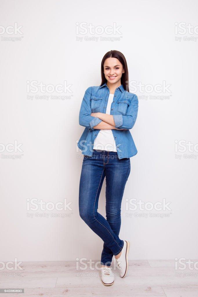 Muito jovem, de jeans e camisa em pé com as mãos cruzadas contra o fundo branco - foto de acervo
