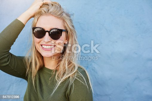 541271164 istock photo Pretty young woman in sunglasses smiling 547512396