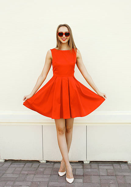 Pretty young woman in the red dress and heart sunglasses stock photo