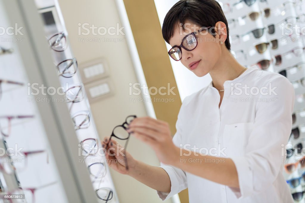 Pretty young woman is choosing new glasses at optics store royalty-free stock photo