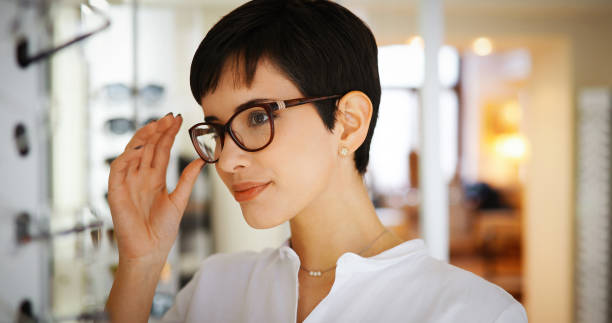 pretty young woman is choosing new glasses at optics store - sale lenses stock photos and pictures