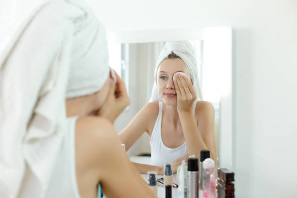 かなり若い女性は彼女の顔を洗浄します。 ストックフォト