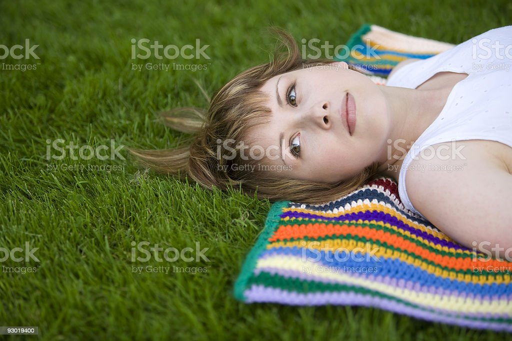 Pretty Young Woman Lies on a Blanket in the Grass royalty-free stock photo