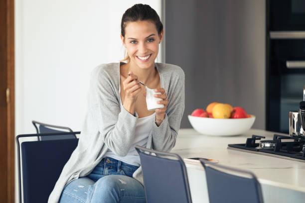 Hübsche junge Frau, die sich die Kamera anschaut, während sie Joghurt in der Küche zu Hause isst. – Foto