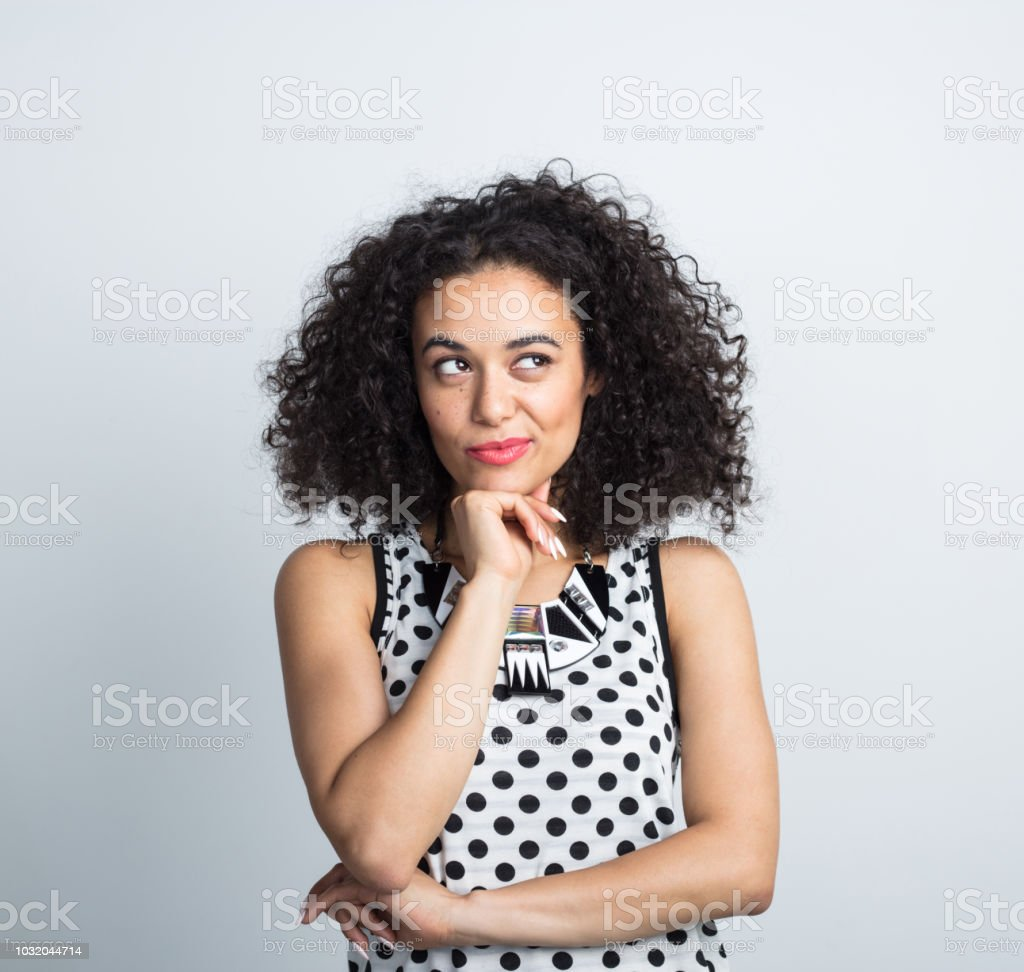 Pretty young woman looking at copy space Close up of pretty young woman with curly hair looking away at copy space with her hand on chin on white background 20-24 Years Stock Photo