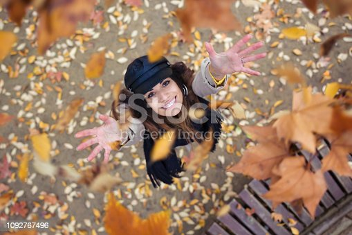 istock Pretty young woman looking to the sky with arms raised as leaves fall from the trees in the park in autumn. 1092767496