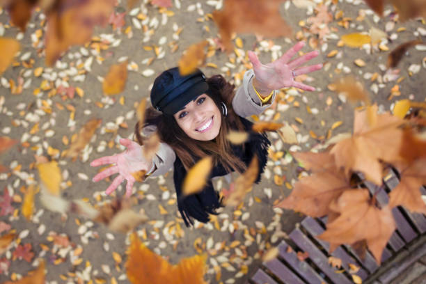 pretty young woman looking to the sky with arms raised as leaves fall from the trees in the park in autumn. - autumn foto e immagini stock