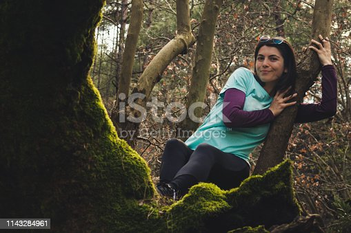 521982322 istock photo Pretty young woman lying on a tree smiling 1143284961