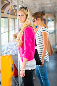 Pretty, young woman on a streetcar/tramway, during her commute to work/school (color toned image; shallow DOF)