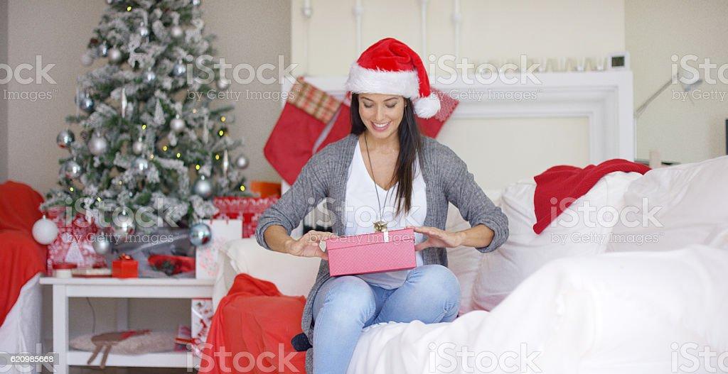 Bela jovem mulher abrindo um presente de natal foto royalty-free