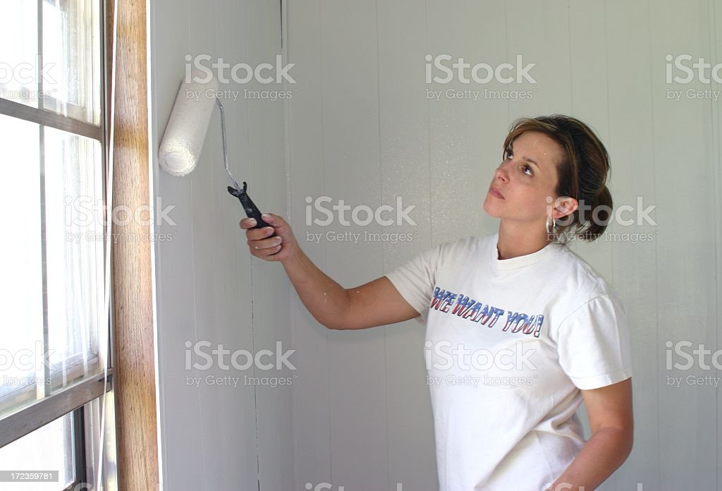 Pretty Young Woman Painting an interior wall by window royalty-free stock photo