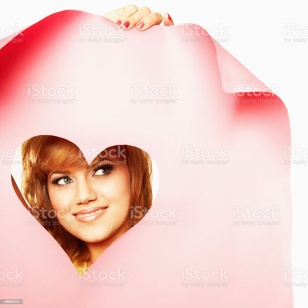 Pretty Young Woman Peeks Through a Paper Heart. Isolated. royalty-free stock photo