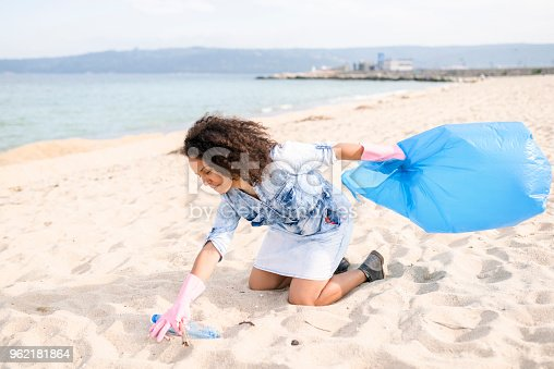 962184460 istock photo Pretty young woman picking up garbage during local clean up 962181864