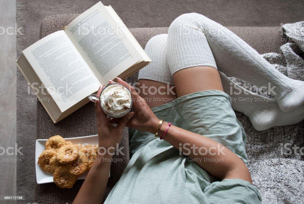 mooie jonge vrouw lezen boek thuis op de Bank met warme chocolatemilk en cookies foto