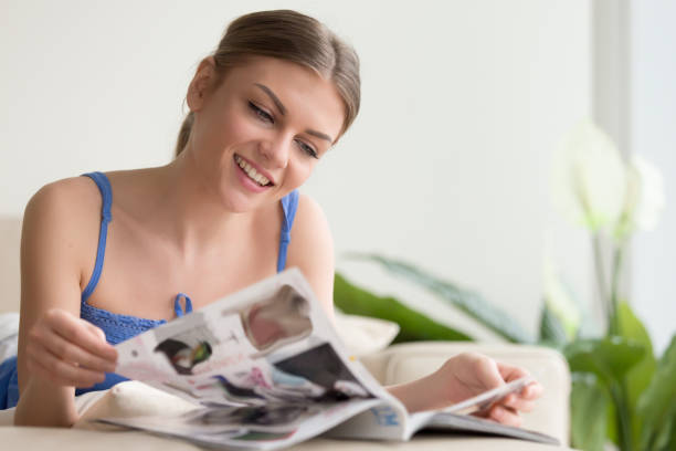 Pretty young woman reading magazine at home Smiling carefree young woman lying on sofa in living room at home flipping magazine pages. Relaxed happy lady reviewing fashion season latest trends, examining, choosing goods in supermarket catalog catalog stock pictures, royalty-free photos & images