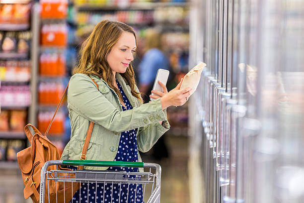 pretty young woman reads label in grocery store aisle - happy person buy appliances stock photos and pictures