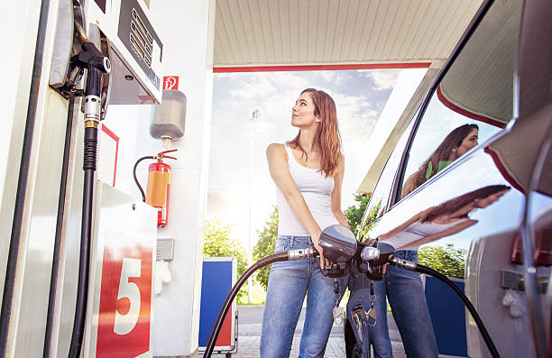 pretty young woman refuel the car - station stock pictures, royalty-free photos & images