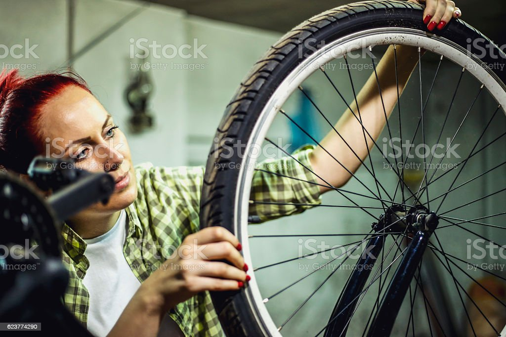 Pretty young woman repairing bicycle wheel in garage stock photo