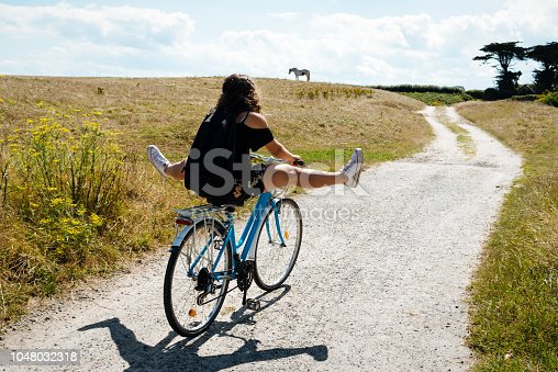 Pretty young woman riding bicycle in a country road with her legs in the air