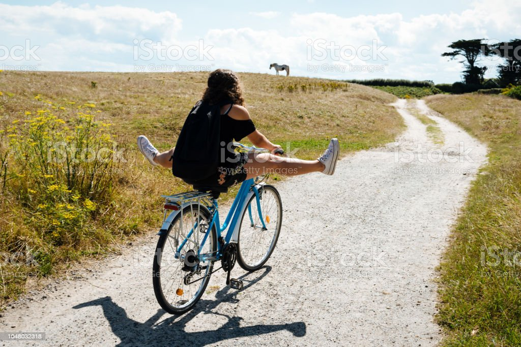 Pretty young woman riding bicycle in a country road stock photo