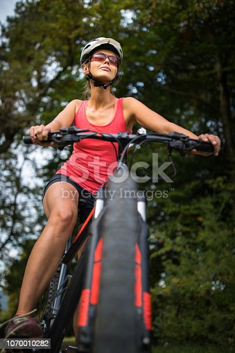 Pretty, young woman riding her mountain bike on a forest path. Enjoying active leisure time outdoors.