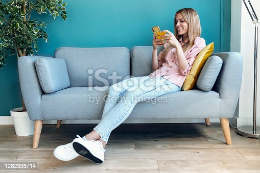 Shot of pretty young woman shopping online with credit card and smartphone while sitting on sofa at home.