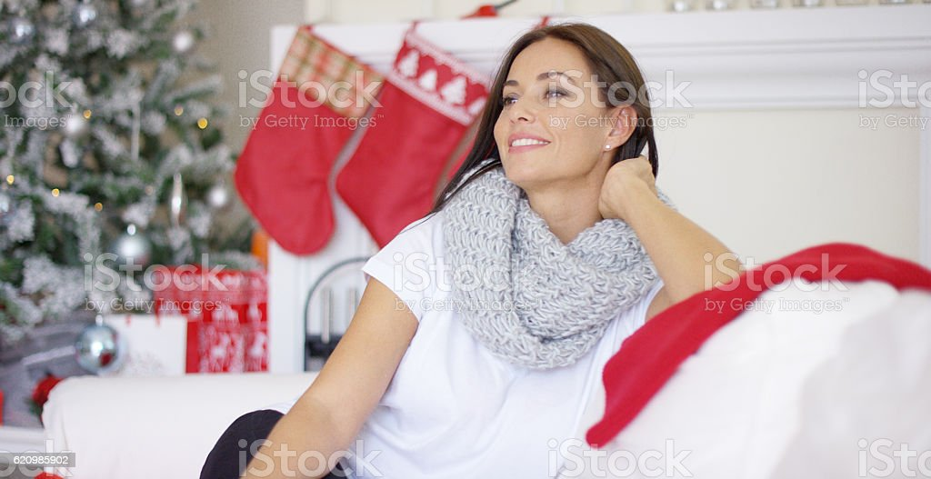 Pretty young woman sitting dreaming of Christmas foto royalty-free