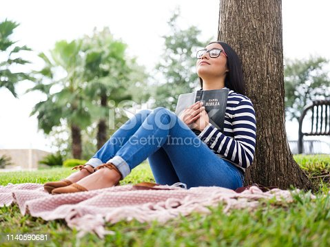 Pretty young woman sitting next to a tree and holding a bible close to her chest.