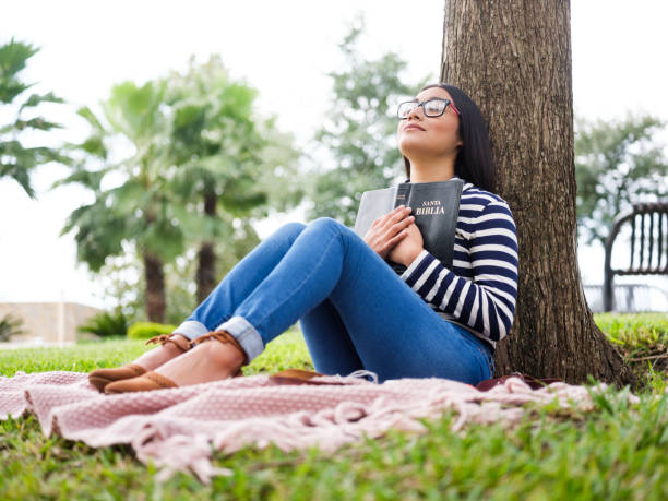 Pretty young woman sitting next to tree and holding Bible stock photo