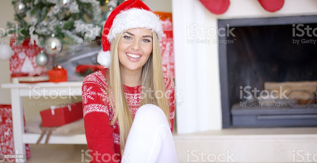 Pretty young woman sitting on the floor with christmas tree foto royalty-free
