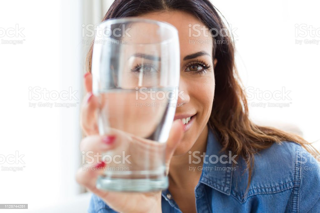 Pretty young woman smiling while looking at the camera through the glass of water at home.