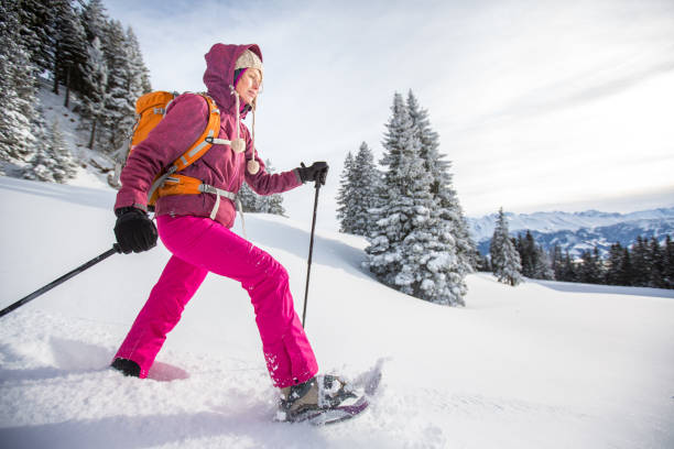 Pretty, young woman snowshoeing in high mountains Pretty, young woman snowshoeing in high mountains, enjoying splendid winter weather with abundance of snow trentino alto adige stock pictures, royalty-free photos & images