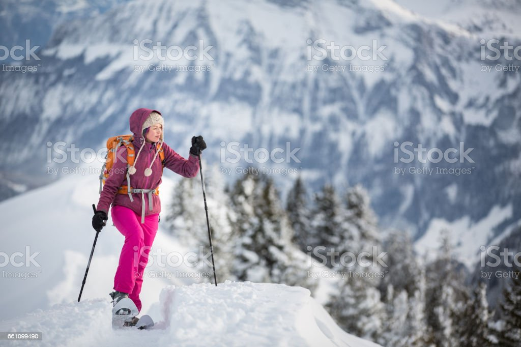 Pretty, young woman snowshoeing in high mountains stock photo
