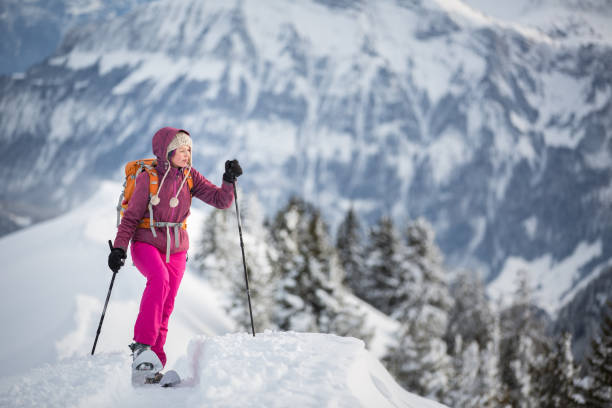 pretty, young woman snowshoeing in high mountains - raquette photos et images de collection