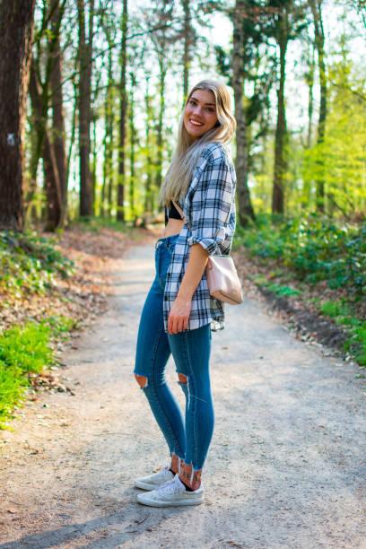 Die hübsche junge Frau steht lächelnd auf einem Waldweg. – Foto