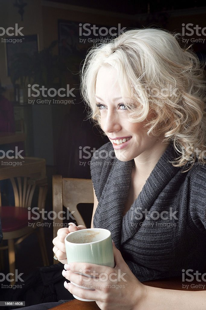 Pretty young woman talking over a cup of coffee royalty-free stock photo