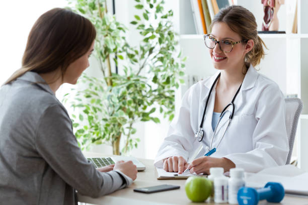 Pretty young woman talking with dietician about her health in the consultation. stock photo