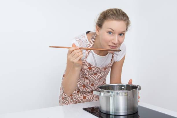 hübsche junge frau, die heißen suppe in küche testen - pfannen test stock-fotos und bilder