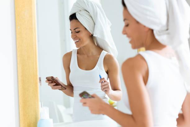 mooie jonge vrouw met behulp van haar mobiele telefoon terwijl haar tandenpoetsen in de badkamer thuis. - cell phone toilet stockfoto's en -beelden