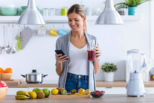 istock Pretty young woman using her mobile phone while drinking fruit juice in the kitchen at home. 1190896826