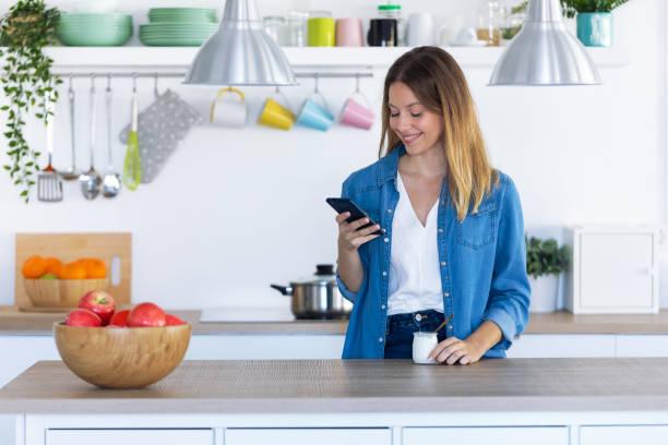 Hübsche junge Frau mit ihrem Handy beim Essen Joghurt in der Küche zu Hause. – Foto
