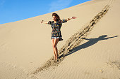 Pretty young woman walking in the sand dunes.
