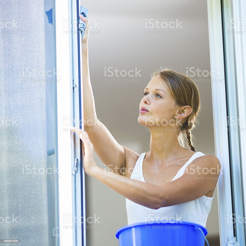 Pretty, young woman washing windows stock photo
