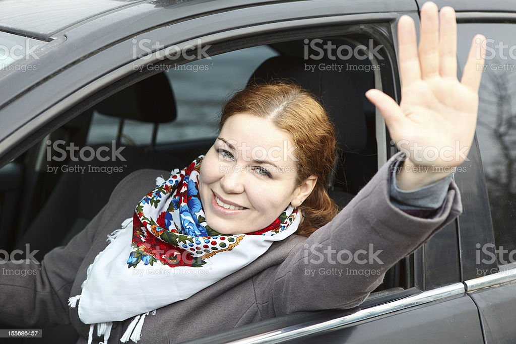 Pretty young woman waving hers hand sitting in car royalty-free stock photo