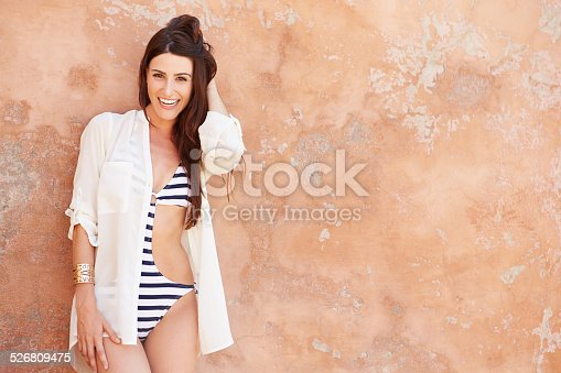 Pretty Young Woman Wearing Swimsuit Leaning Against Wall Smiling To Camera