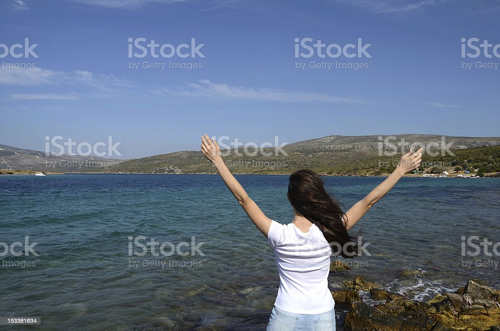 Pretty young woman with arms raised stock photo