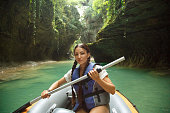 pretty young woman with dark hair gathered in two black braids, lady looks and poses for camera in life jacket and paddle in hands, tourist in inflatable boat sails through Martvili Kanyon Georgia.